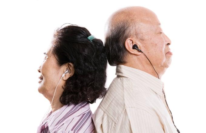 Senior asian couple listening to music