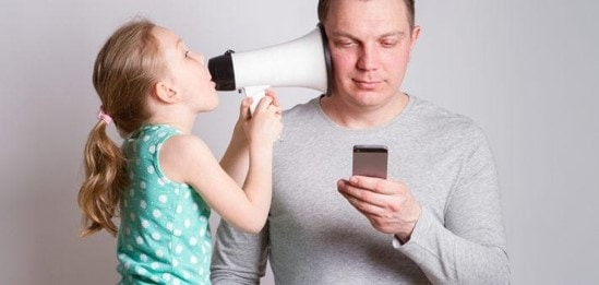 a child testing a man's hearing with a megaphone.